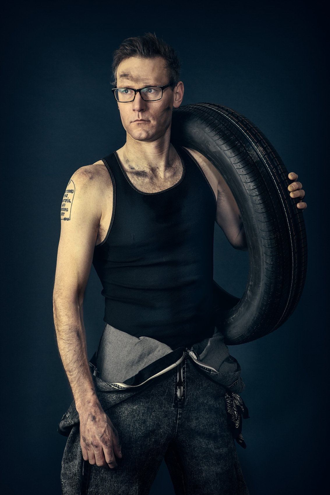 Portrait of man holding a tire photographed by Dave Rentauskas