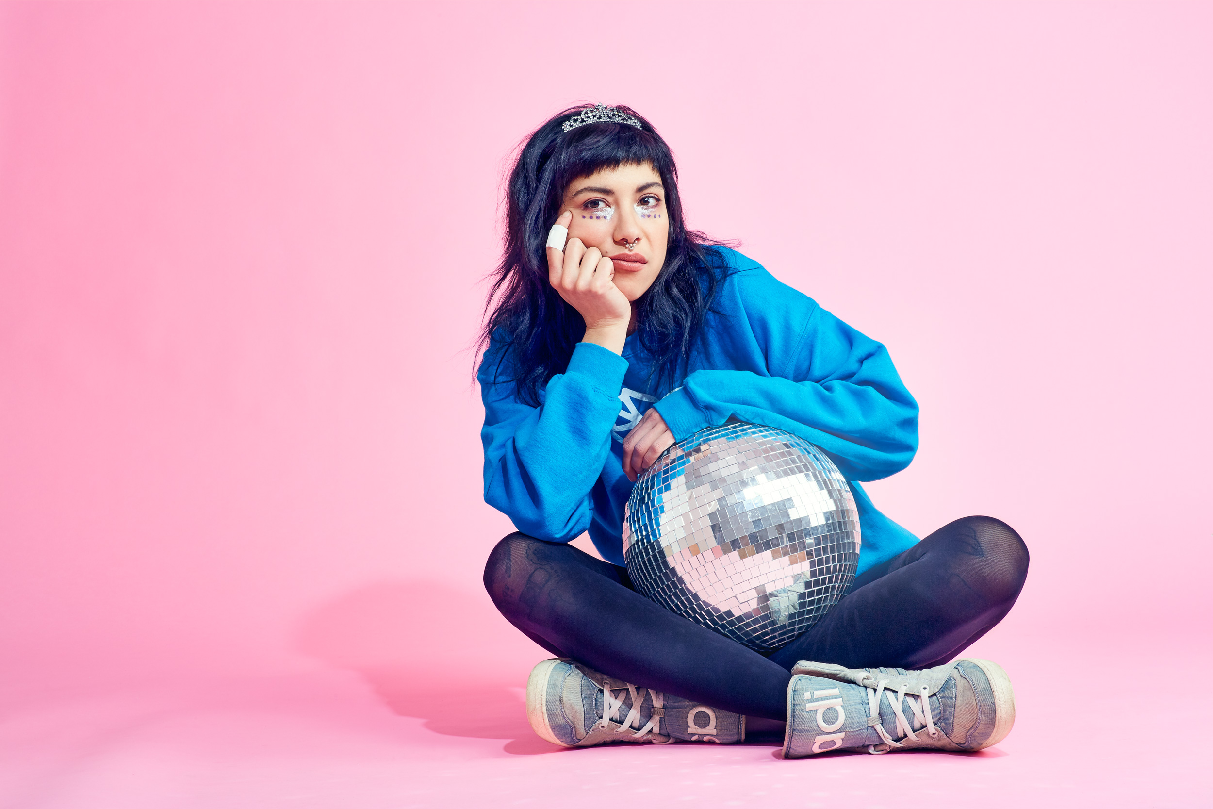 Portrait of a girl with disco ball on pink background photographed by Dave Rentauskas
