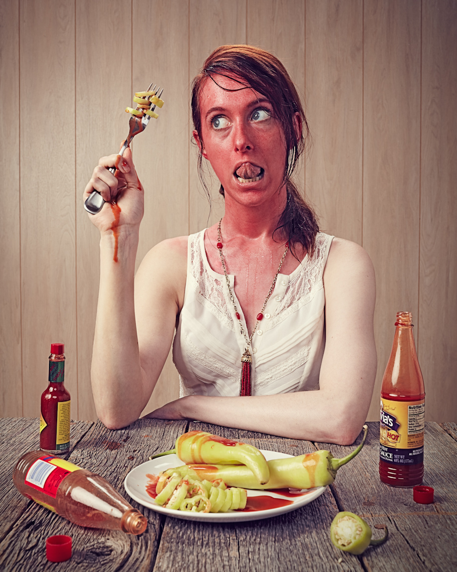 Conceptual portrait of a woman eating hot peppers and sweating photographed by Dave Rentauskas